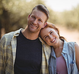 Middle-aged couple smiling and leaning their heads together outdoors