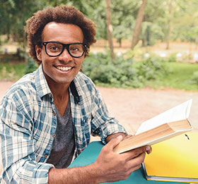 Young man with glasses smiling and reading outdoors