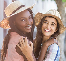 Two young women smiling and wearing hats outdoors