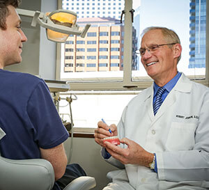 Young male patient and elderly male dentist smiling as they look at prosthetics