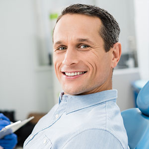 Middle-aged man smiling in the dental chair