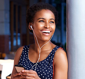 Young woman smiling with earbuds in